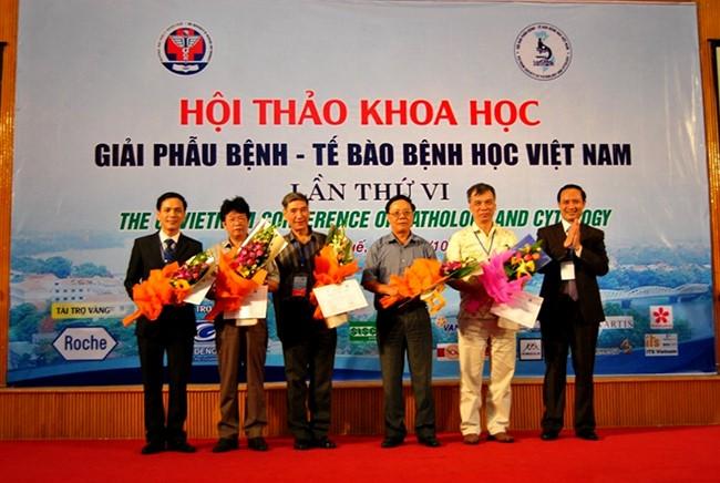 PGS.TS. Trịnh Tuấn Dũng tặng hoa và giấy chứng nhận cho các chủ tọa của một phiên báo cáo khoa học trong Hội thảo
