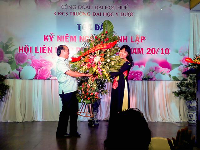GS.TS Võ Tam, Phó Bí thư Đảng ủy, Phó hiệu trưởng trao tặng lẵng hoa của Đảng ủy, Ban Giám hiệu Trường cho nữ CBVC Trường